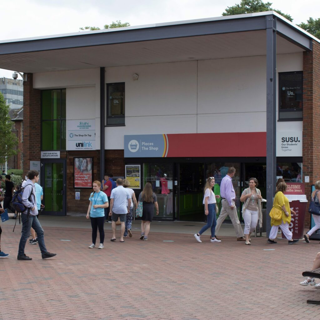 A photo of the exterior of The Shop at Highfield campus. Lots of people are walking past the entrance.